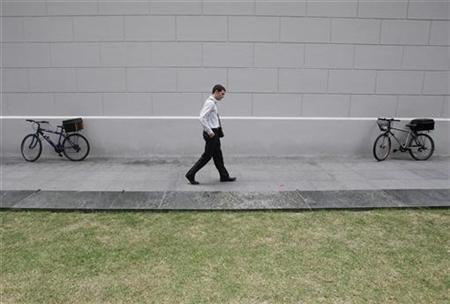An office worker walks outside a train station during lunch time in Singapore's financial district January 22, 2009. REUTERS/Vivek Prakash